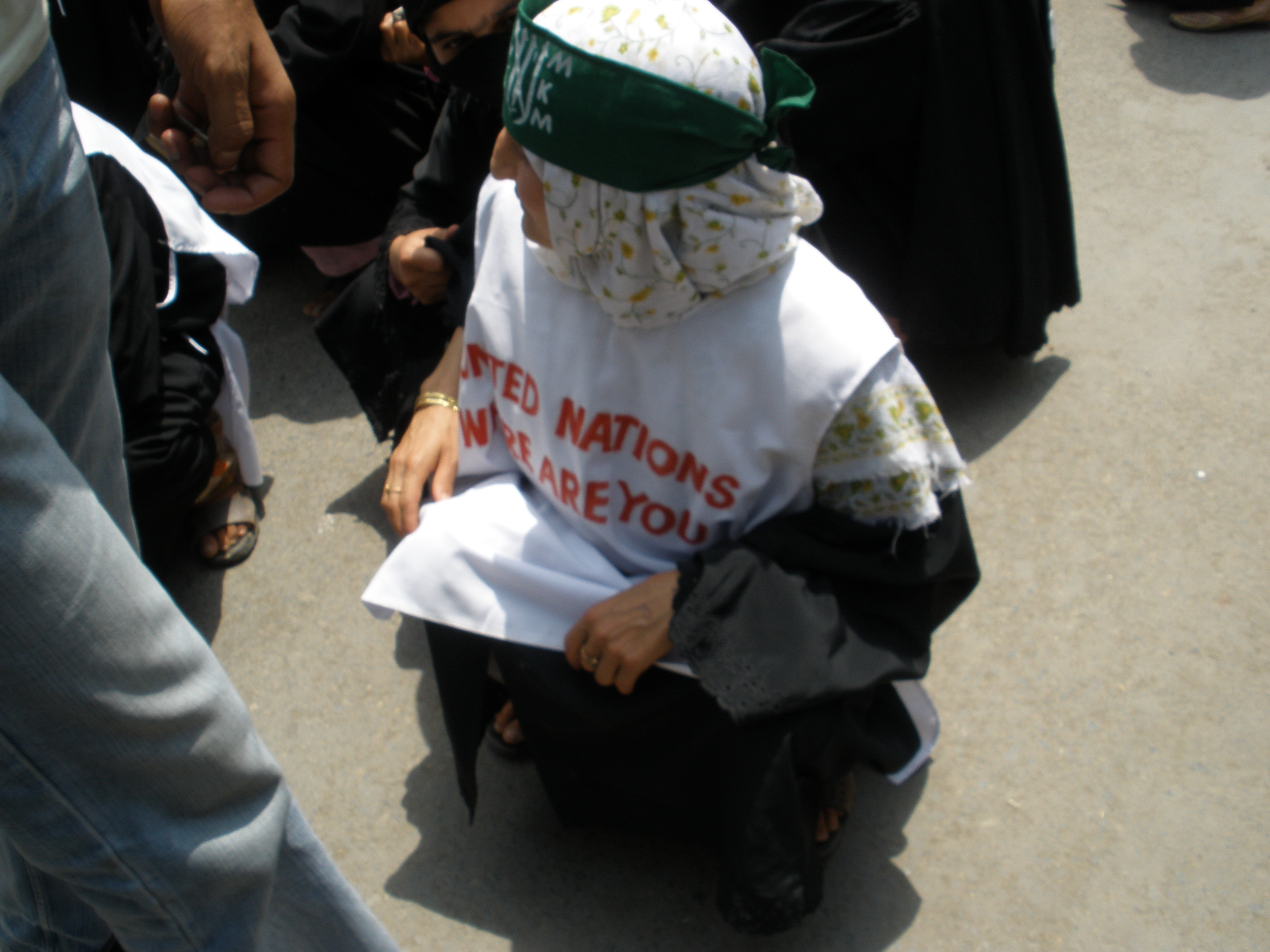 A protester kneels to the ground in a white banner calling on the international community to pay attention.